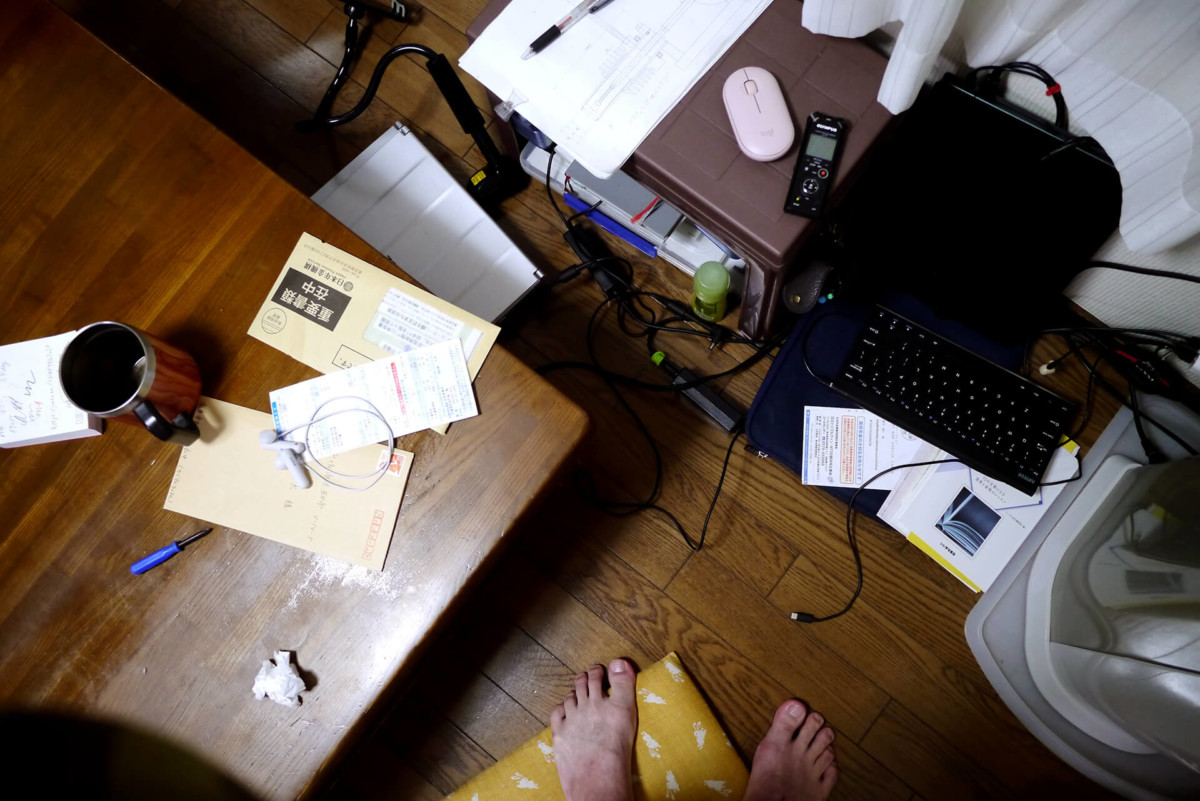 Messy table, computer and foot