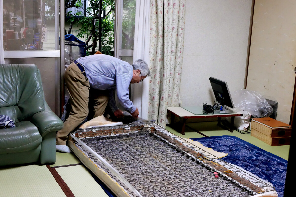 A elder man is dismantling the bed mat in Japan
