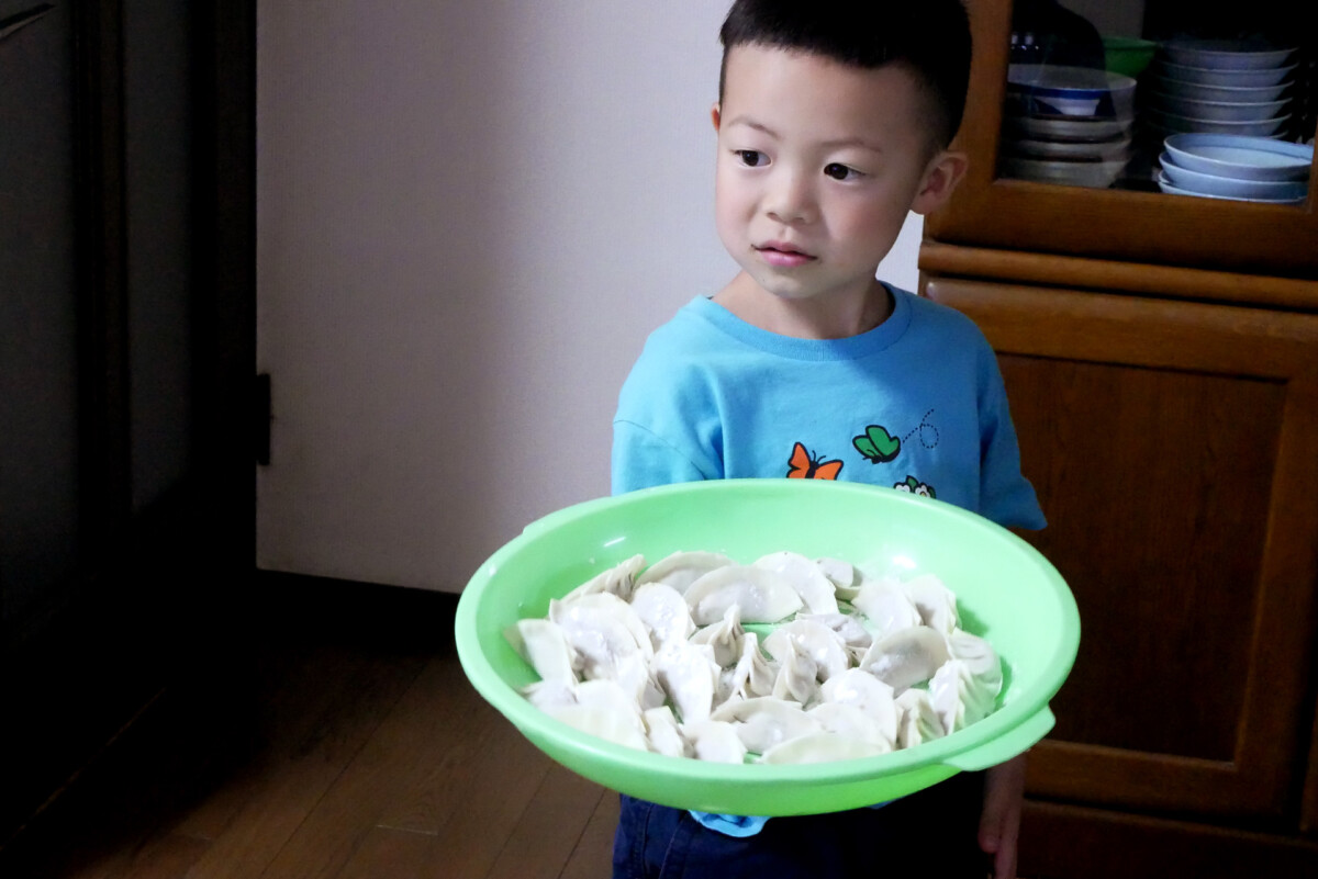 A boy have a lot of gyoza of plate at the Japanese family home