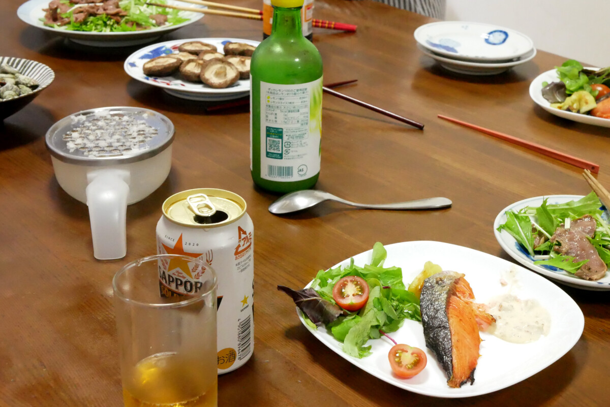 Canned Beer, salmon fillet and grilled mushrooms at Japanese family on the table in Hiroshima Japan