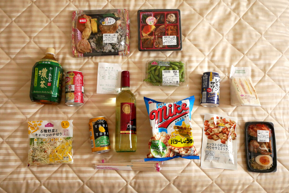 Japanese side dishes, bento boxes, medicines, etc. lined up on the hotel bed