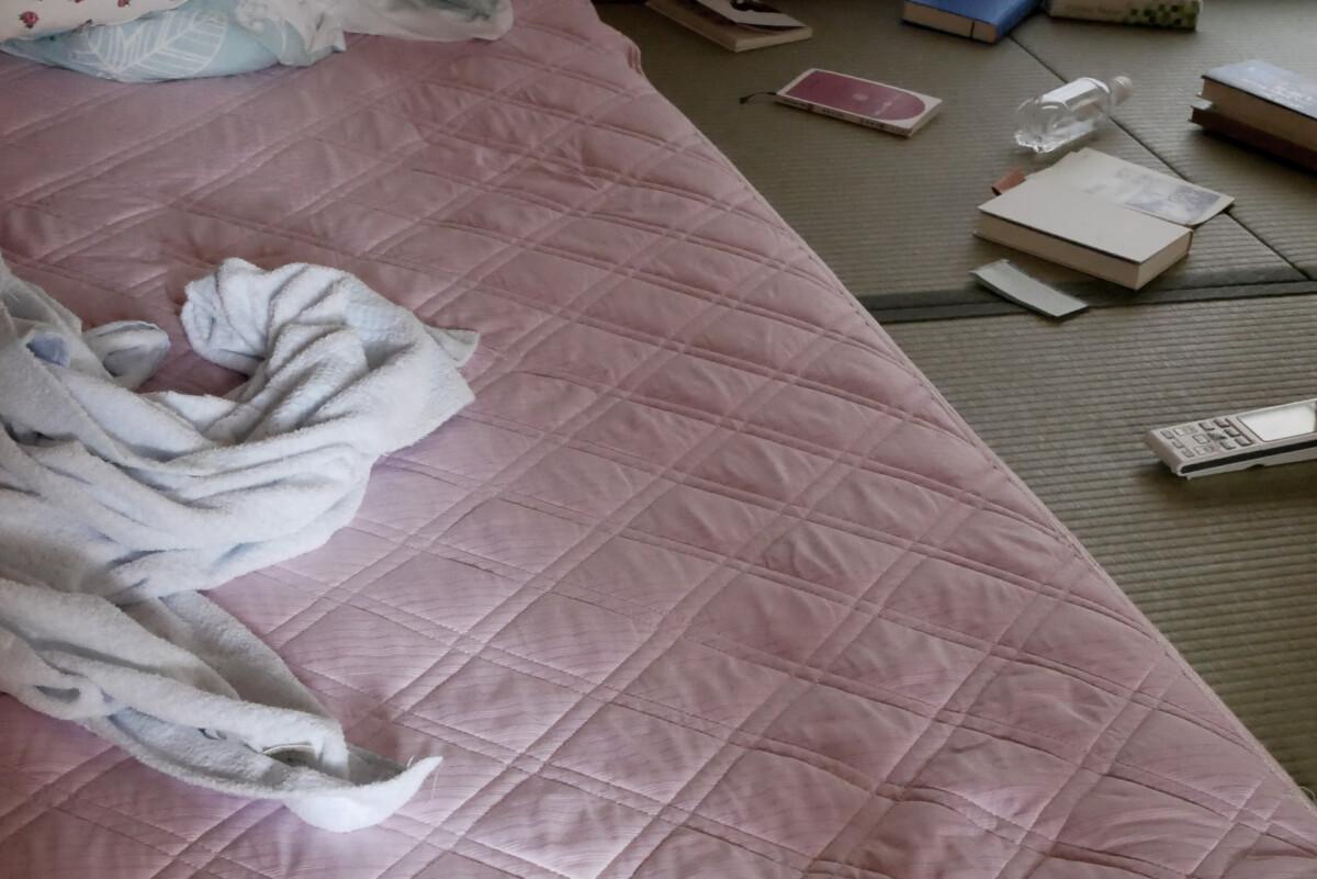 Messy futon mat on traditional Japanese tatami mat