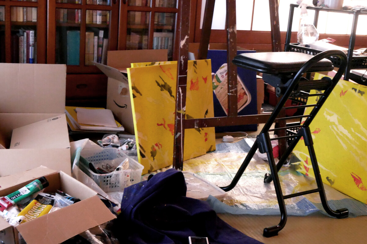 There are paintings, a chair etc. Japanese artist's messy studio in Hiroshima Japan