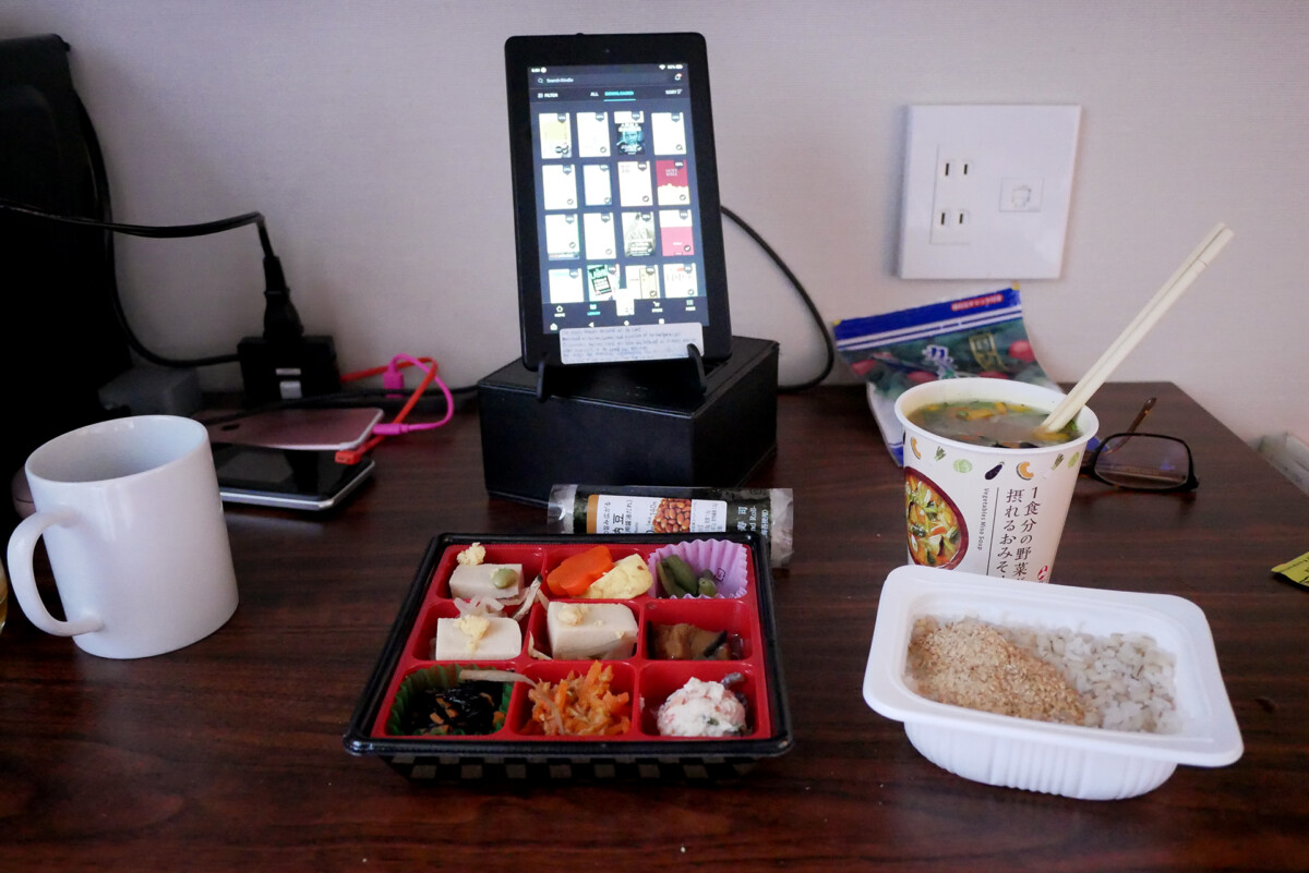 Japanese bento dishes, instant rice, miso soup, tablet kindle fire on the desk at at hotel room in Hiroshima Japan