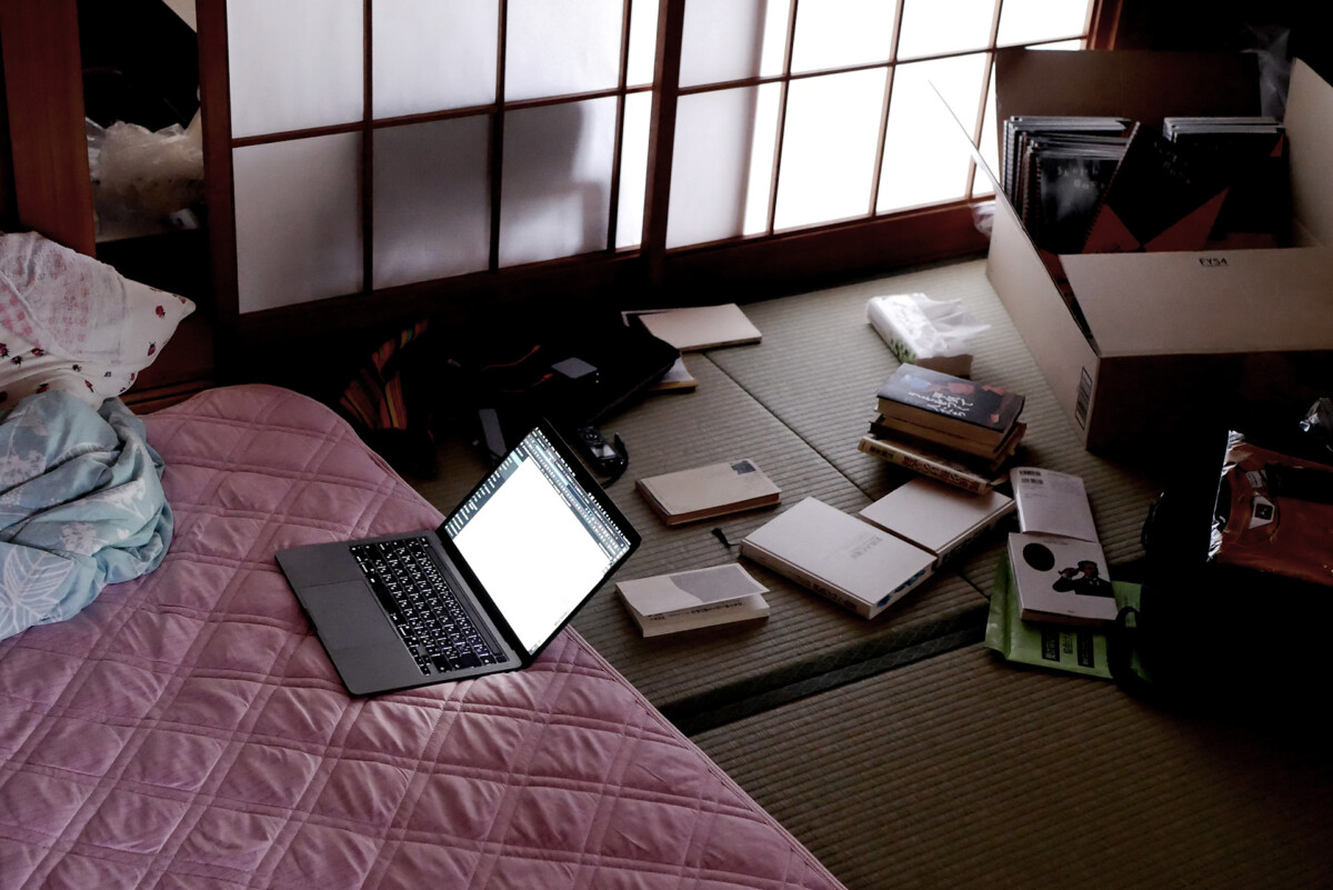 MacBook Pro on the futon and messy tatami mat room
