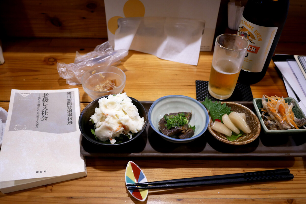 Japanese Izakaya small dishes and a Japanese book on the wooden table