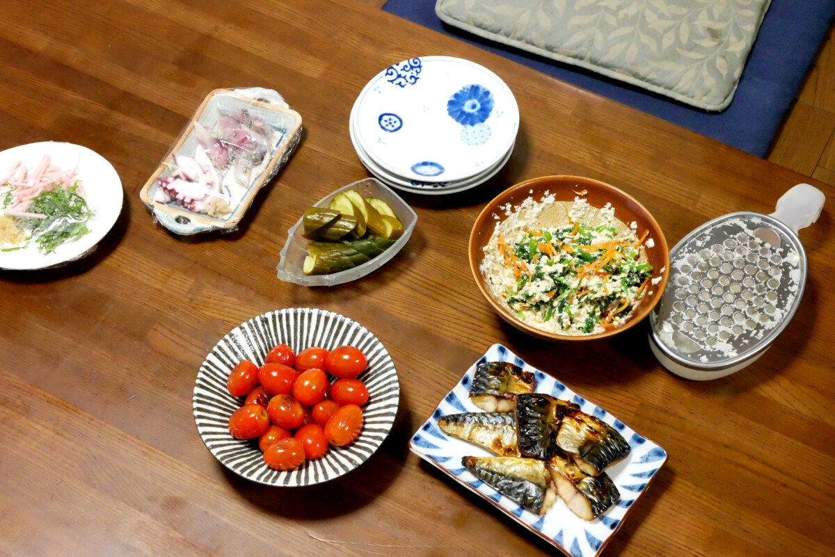 Tomato, grilled mackerel, shiraae, etc Japanese dishes are on the wooden table in Hiroshima Japan
