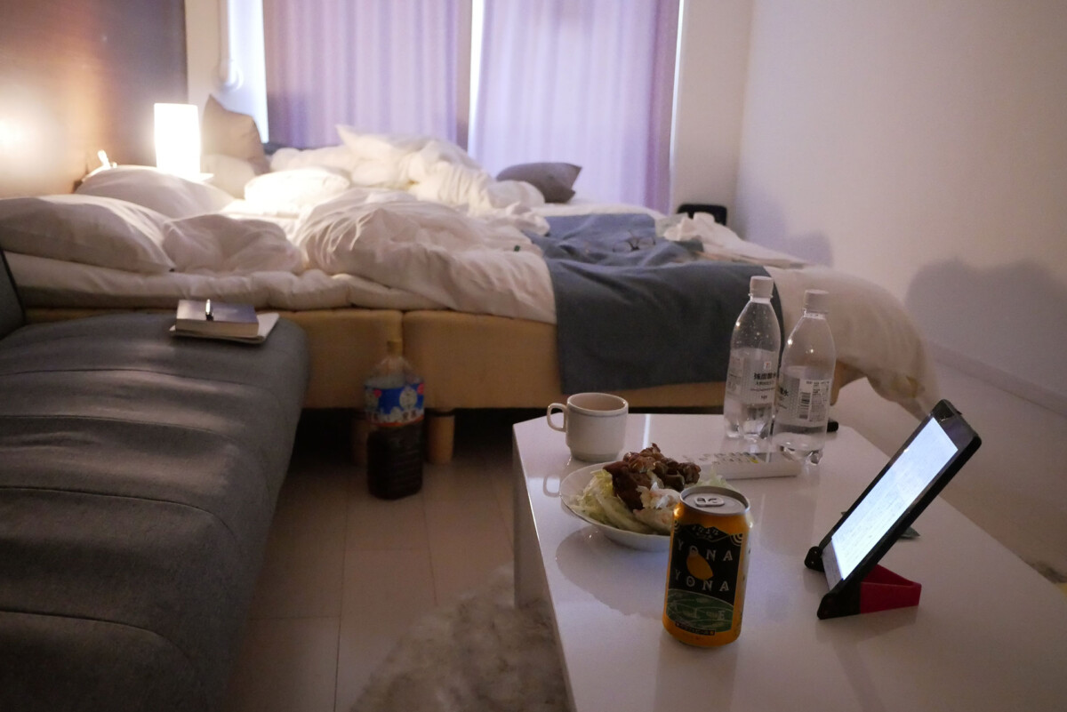 two beds, food and canned beer on the table in the evening at my home like hotel room in Hiroshima Japan