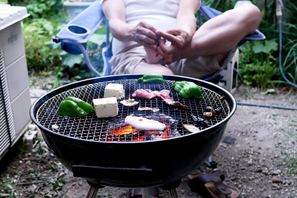 Beef, bell peppers etc on the Charcoal Grill at yard, there is a man's legs in Japan