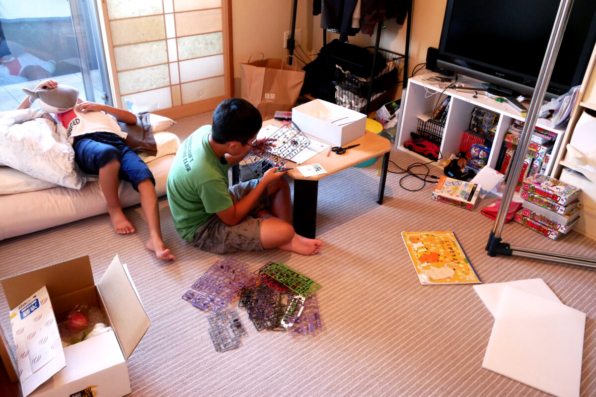 A boy making evangelion plastic model and another boy lying the futon mat in the room in Hiroshima Japan