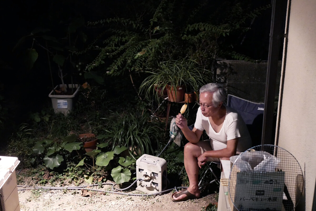 An old Dad is sitting a chair and eating ice candy in the dark night at yard