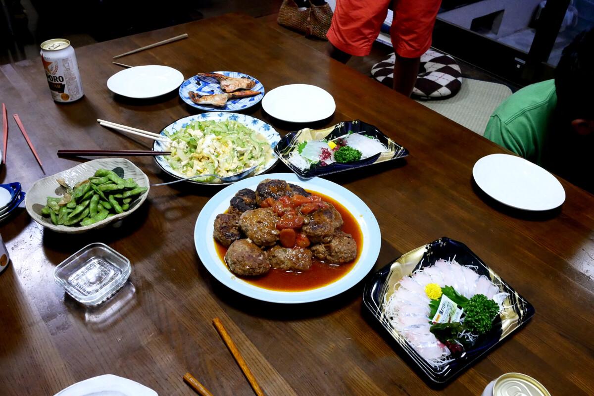 Japanese dinner like sashimi, fried goya, hamburger steak on the wooden table