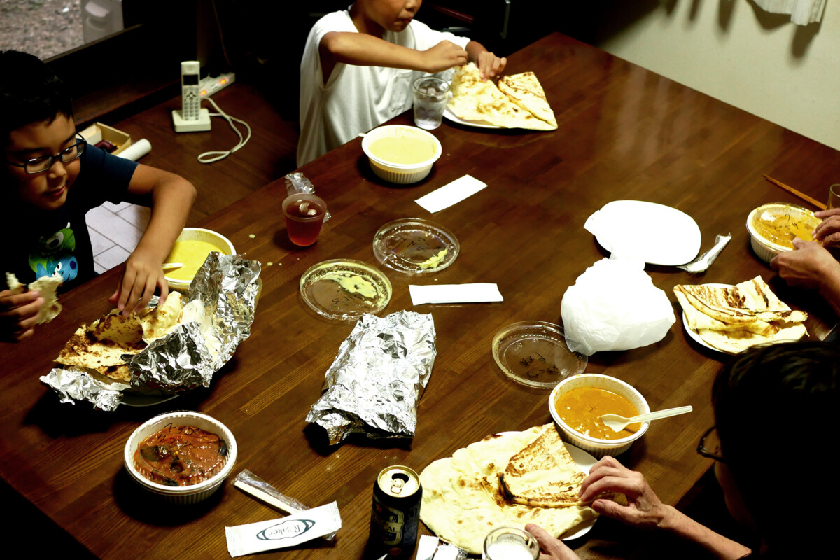 A Japanese family member are eating Indian curry and naan on the table