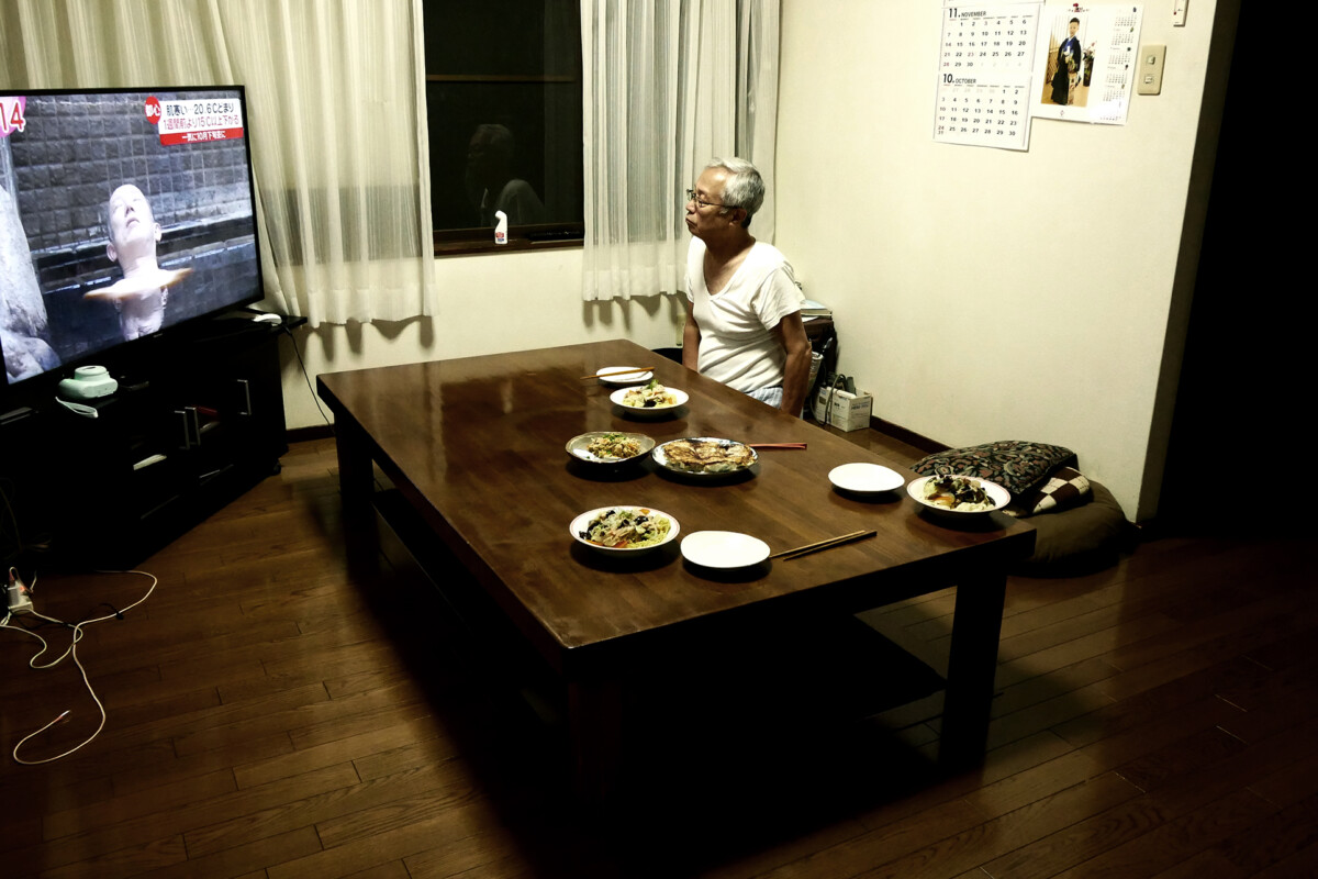 An elder man who is my father is watching TV at a dining room's table