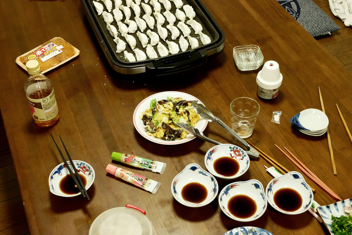Gyoza on the electric plate, sauce dip, and fried egg on the wooden table