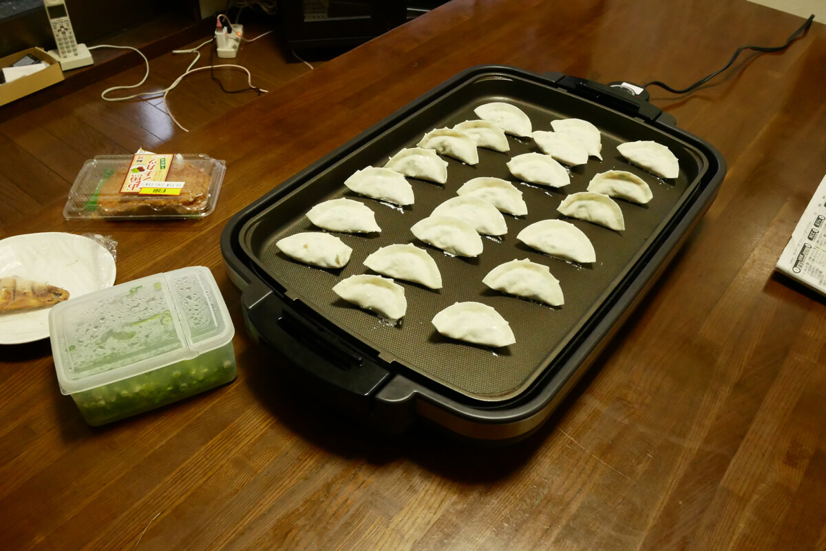 Japanese hand maid gyoza on the electrical plate on the wooden table