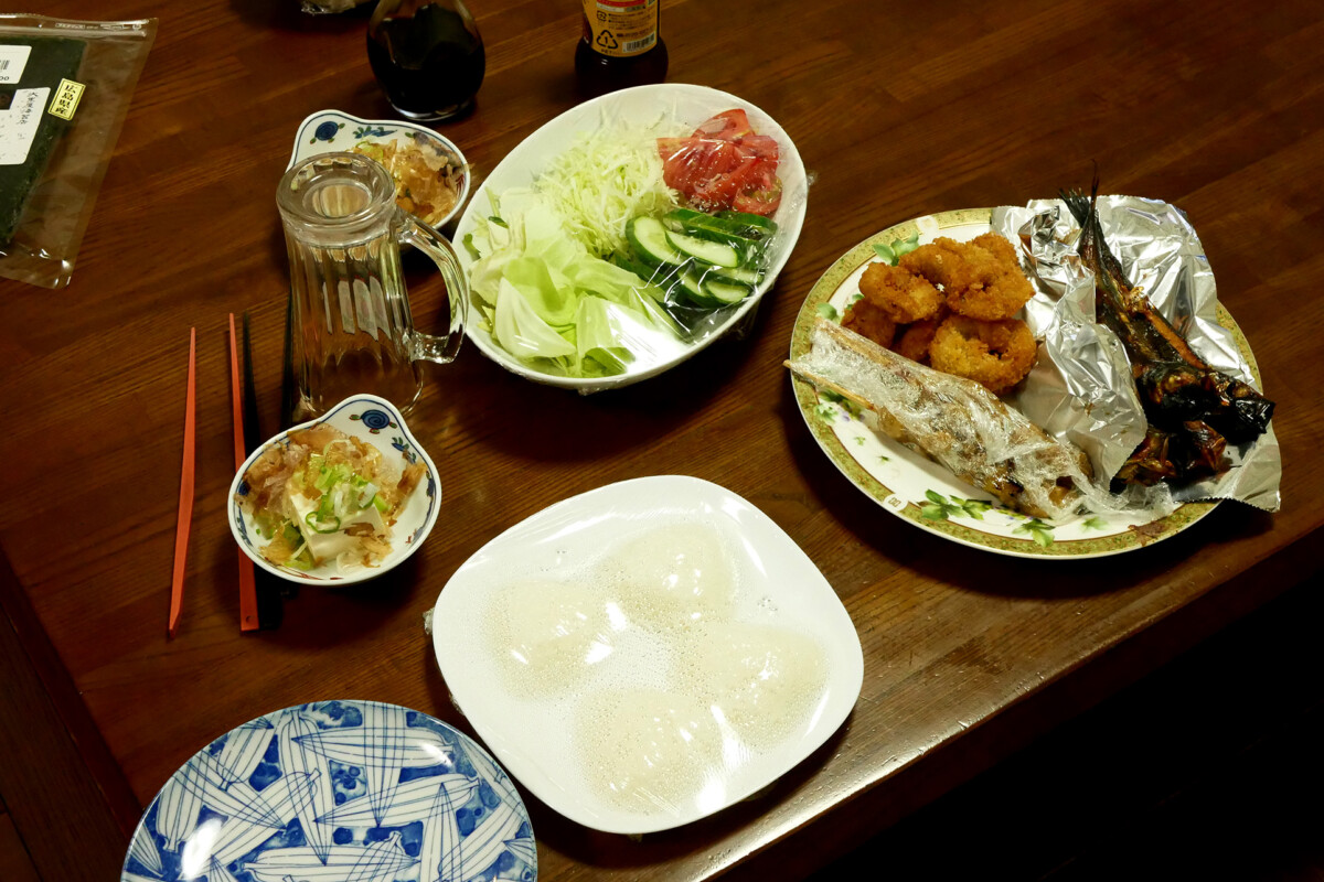 Salad, grilled fish, rice ball such Japanese daily dishes on the wooden table