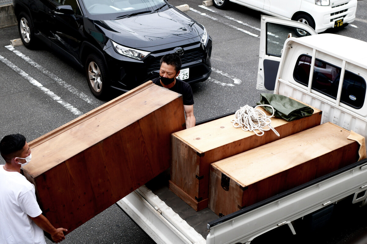 Men are moving a chest on the lightweight truck