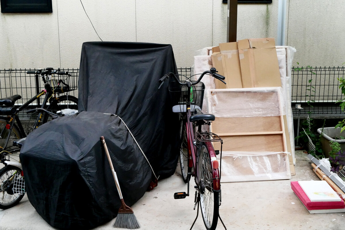 A covered motor bike, a bicycle and paintings on the yard