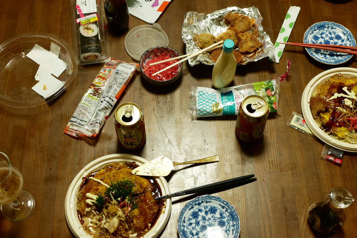 Packed Hiroshima style Okonomiyaki, canned beer, deep fried pork cutlet etc. on the wooden table