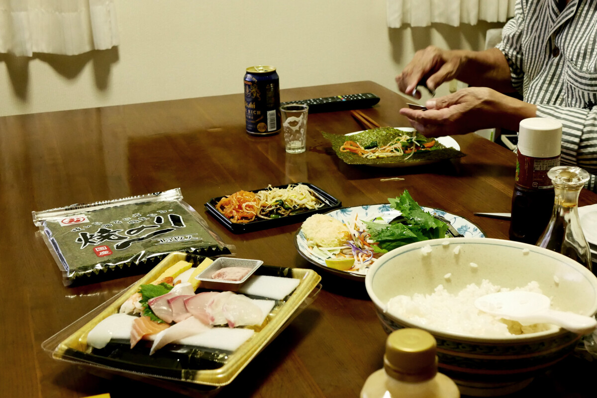 Japanese temaki sushi dishes on the table, an old man who is making sushi