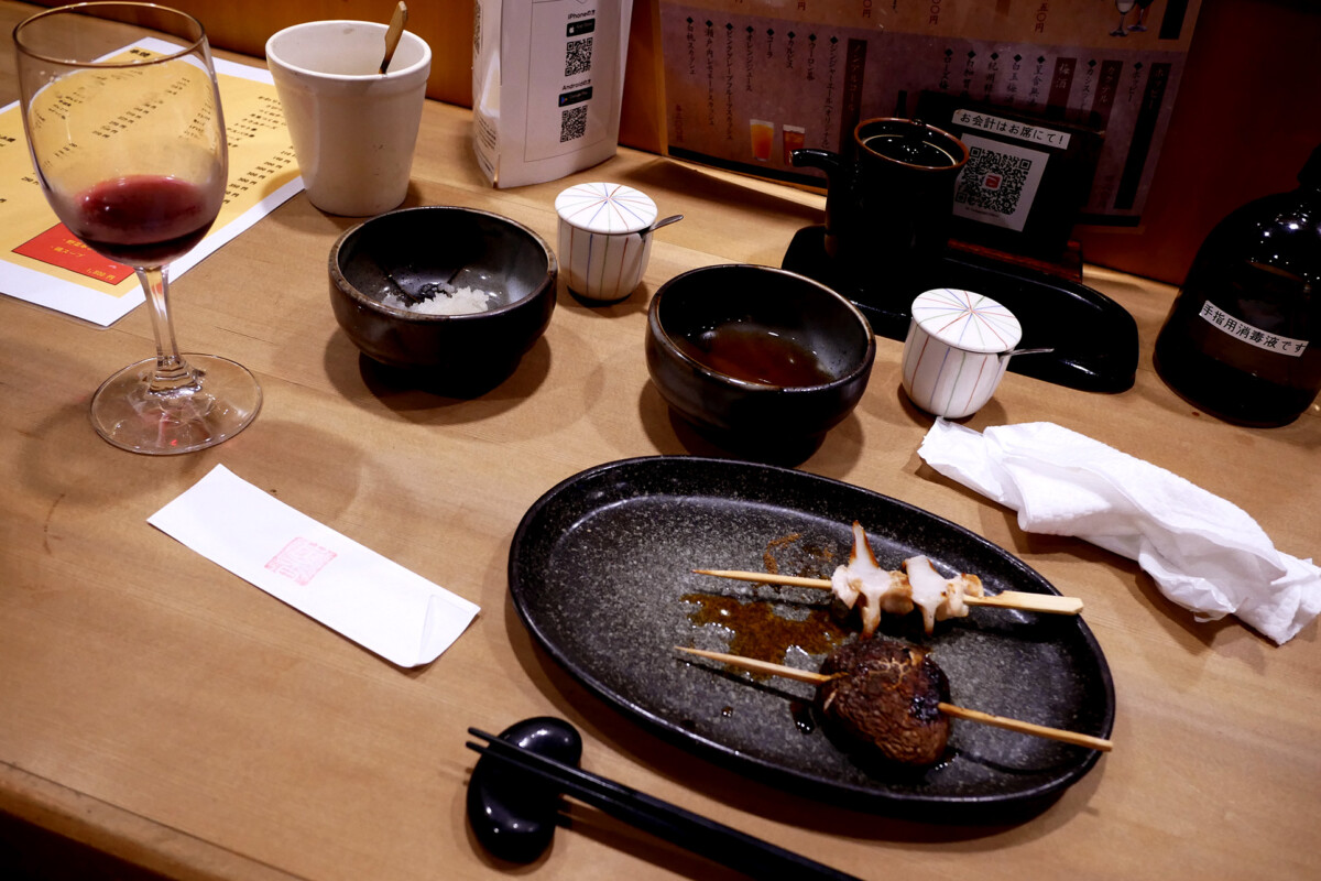 Japanese yakitori dishes, wine on the wooden counter table