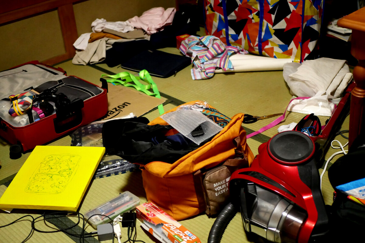 There are canvas, vacuum creaner, a colorful bag on the tatami mat floor