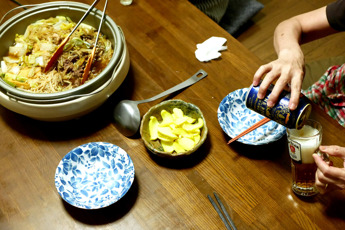 Sukiyaki pot on the table, an elder woman's hand is pouring a canned beer in a glass