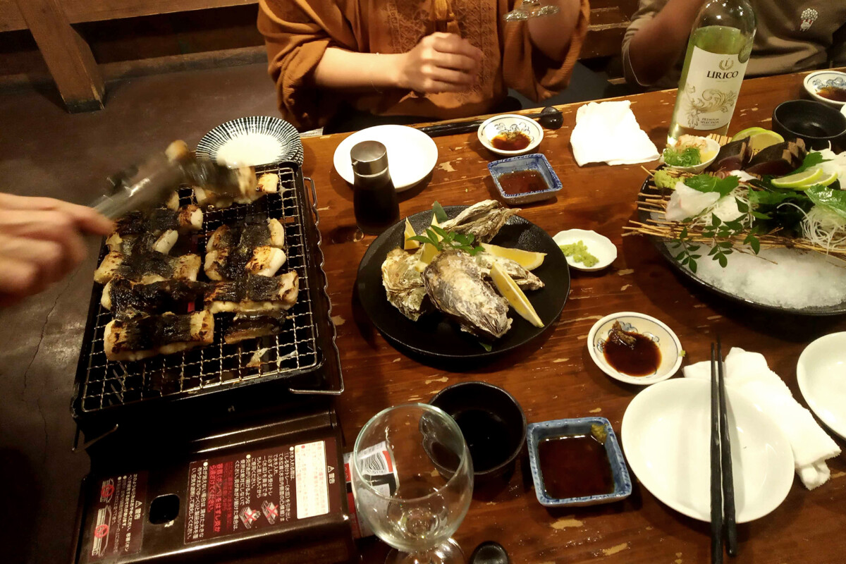 Grilling fresh eel on the fire and sashimi on the table