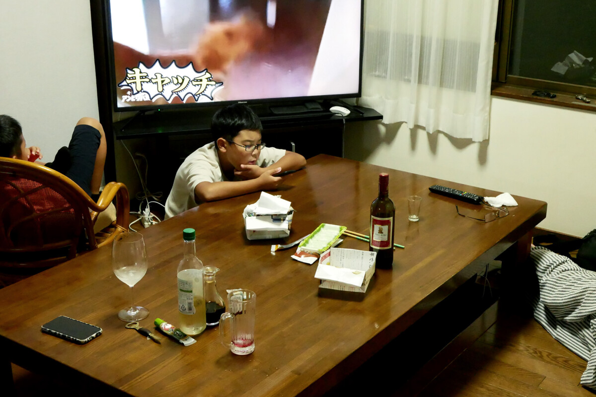 A child is using mobile phone at the table, another child is watching TV, there is a wooden table